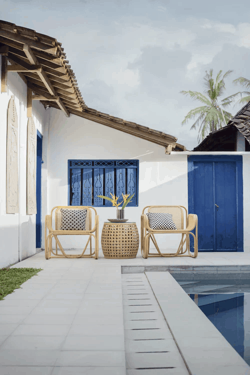 Outdoor wicker furniture on a patio by a pool