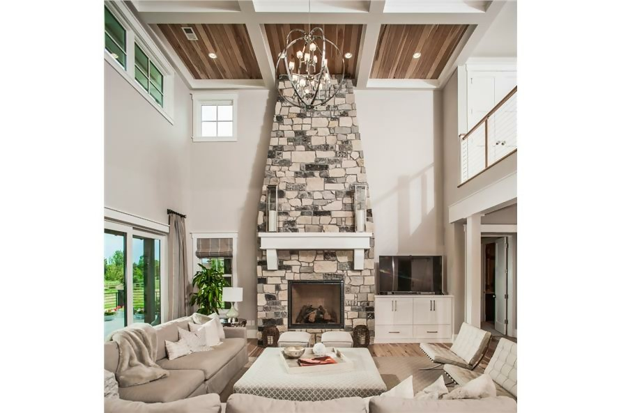 Stone fireplace in Craftsman style home that extends to the 2-story-tall ceiling