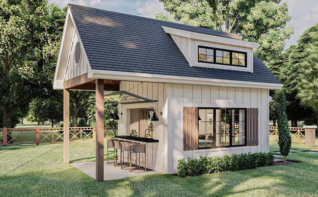 Board-and-batten-sided shed with gable roof, shed dormer, and covered patio with eating/drinking bar and chairs