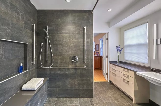 Open bathroom with lots of space and a sink that is clear of obstructions underneath it to accommodate a wheelchair