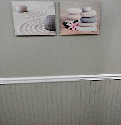 Gray wall with beadboard wainscoting below artwork that hangs above it