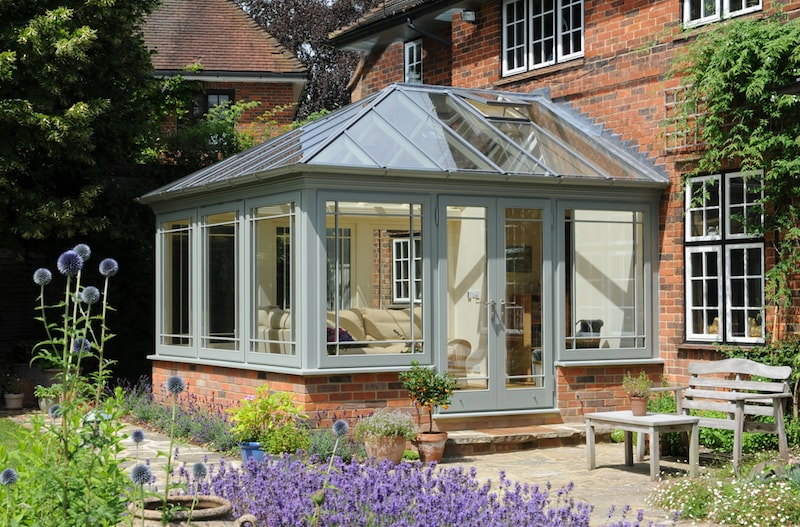 Traditional conservatory on the back of a brick home