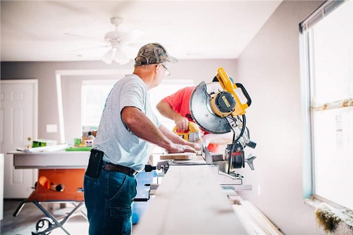 Contractors working in a home with a radial-arm saw and other tools