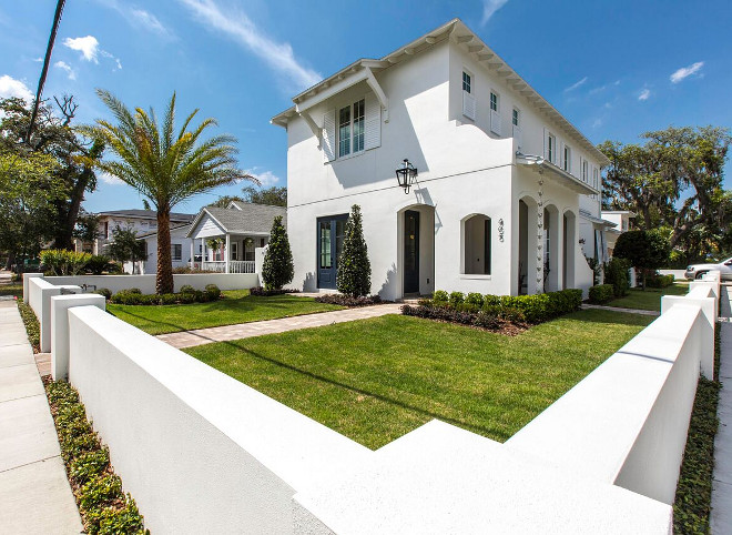 White house on a corner lot with white stucco fence