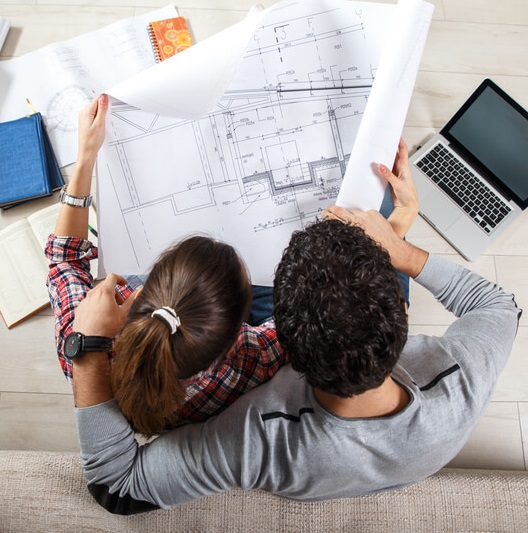 Couple reviewing blueprints for a house
