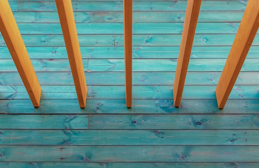 The blue painted stain on this deck contrasted with the natural wood of the deck rail makes the outdoor space pop.