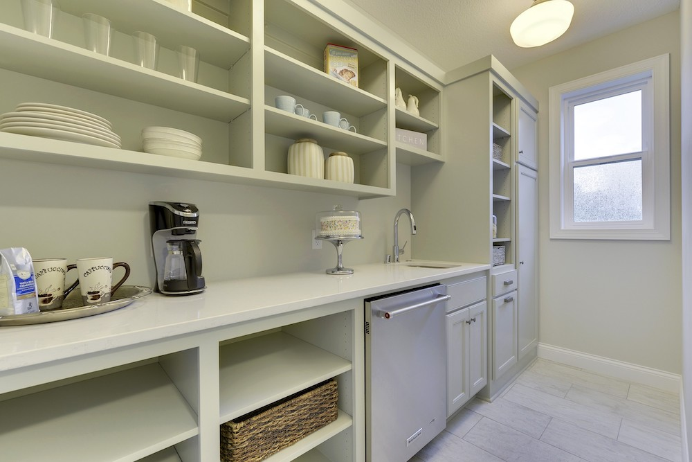 """Out-of-site """"dirty pantry"""" where actual food prep, cleanup, and other work takes place, keeping the main kitchen clean"""