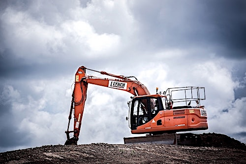 Orange excavator against a cloudy sky