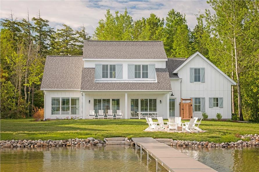 Rear of barn style home with covered back porch and a lake with a dock