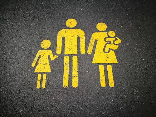 Family of four painted in yellow international symbol style on street