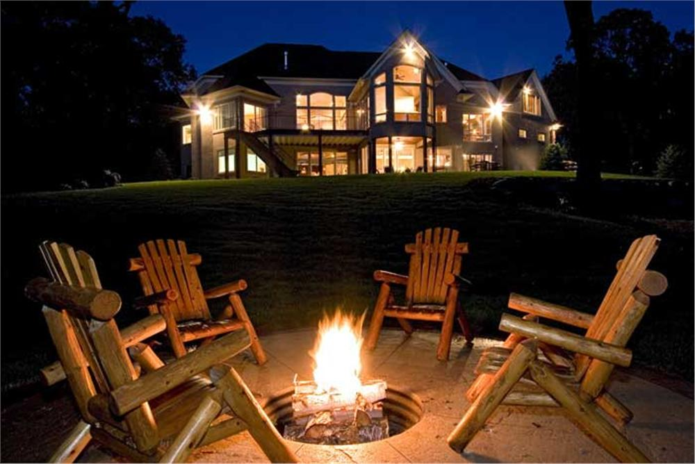 Fire pit ablaze in backyard of this country home.
