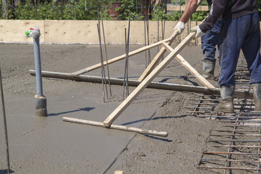 Concrete workers floating a wet, just-poured concrete slab to level it out and make it smooth