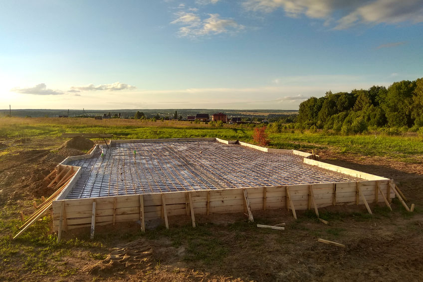 A slab foundation's wooden formwork and wire mesh over gravel waiting for concrete to be poured