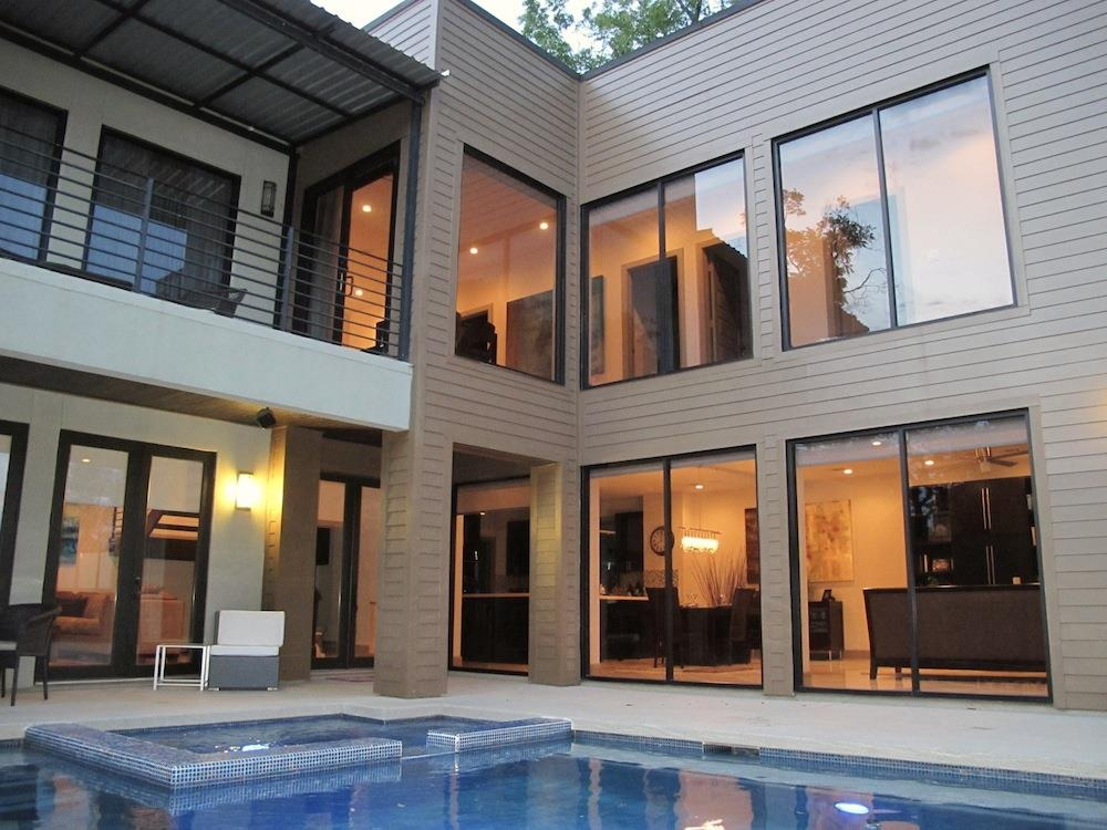 Interior courtyard with pool surrounded by patio and upper balcony/deck