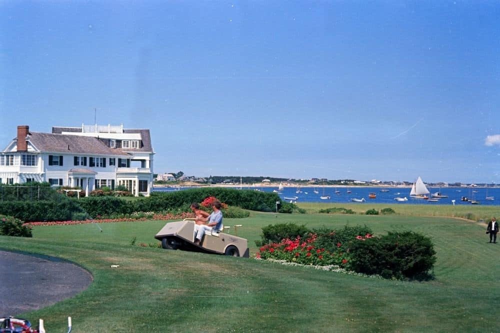 JFK in golf cart at Kennedy Summer White House with view of the main house and ocean in 1963