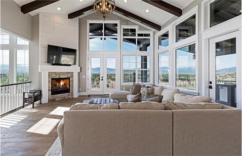 Great Room with vaulted timber ceiling and large windows on three walls