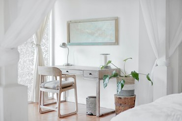 Work corner in a bedroom that's mostly white with subtle splashes of beige