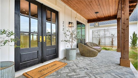 Country style home's covered front porch with natural wood ceiling