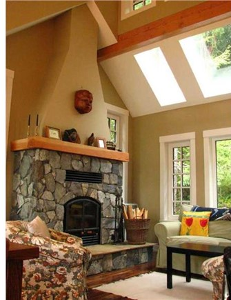Living room with large windows and vaulted ceiling with skylights