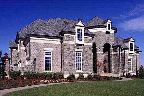 European style home with white rectangular oriel windows supported by corbels