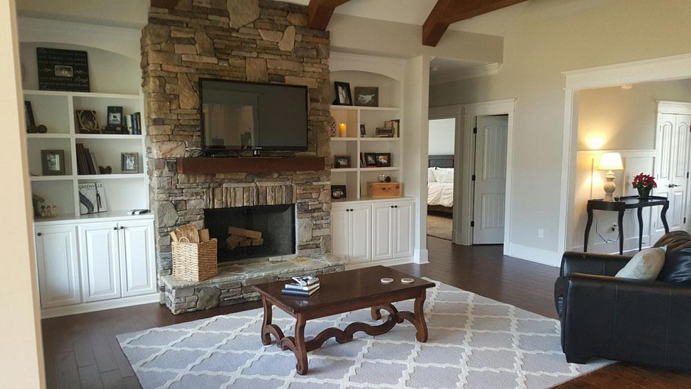 Over-the-fireplace placement of a large-screen TV in a 3-bedroom, 2.5-bath Country home