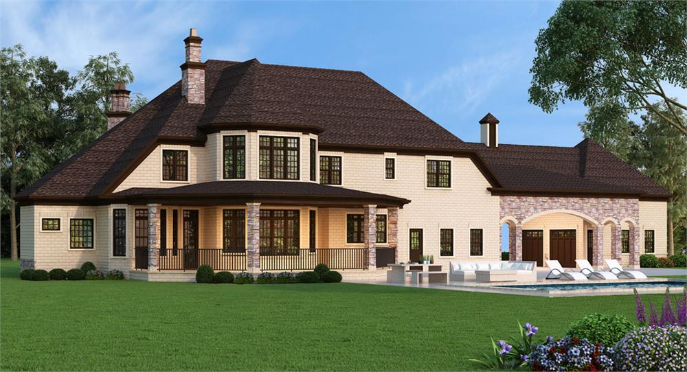 Rear view of luxury European style home with two chimneys and covered rear patio