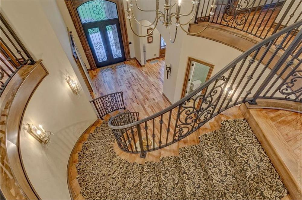 Grand, curving staircase in the foyer of a large home