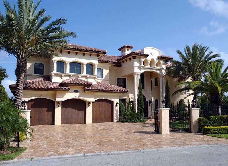 Mediterranean style home with brown tile roof and light-colored stucco siding