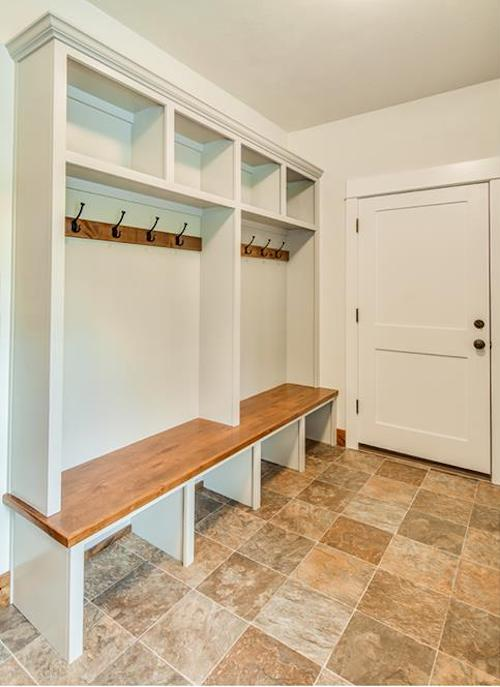 Beautiful mud room with bench, white-painted cubbyholes top and bottom, and coat racks