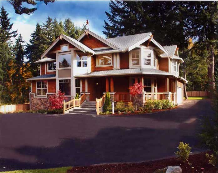 Arts & Crafts style home with red siding and wrap-around porch