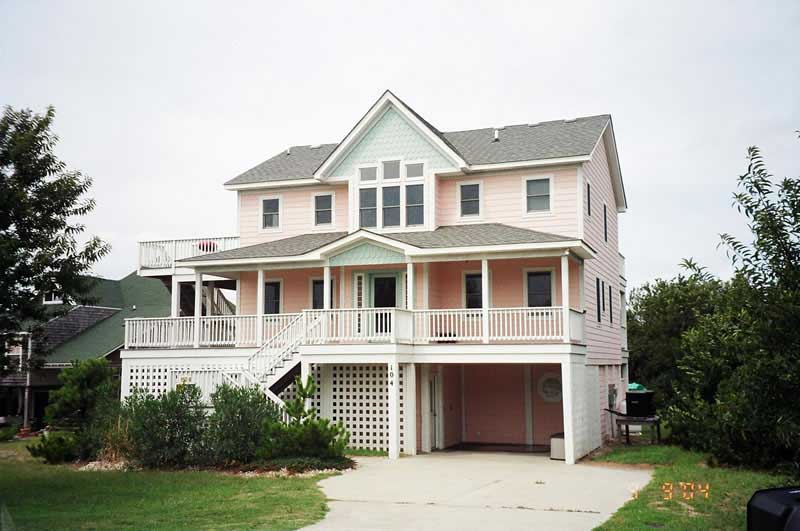 Raised pink beachfront home with front porch and upper-level deck on the left