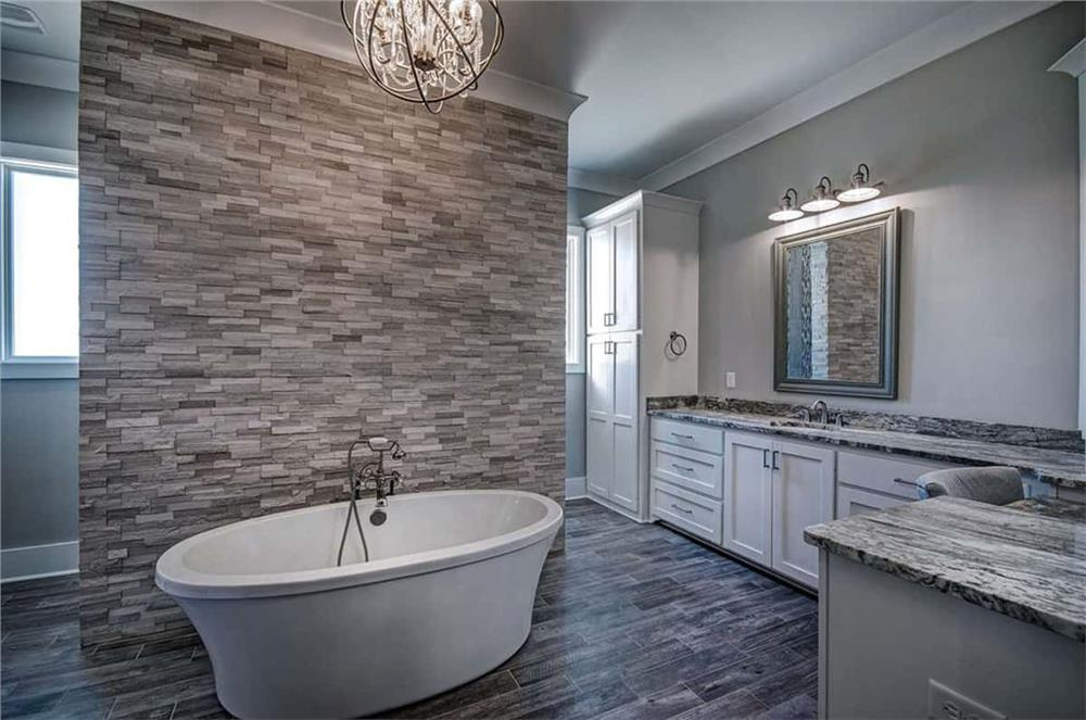 Master bath with stacked-stone accent wall behind a freestanding tub