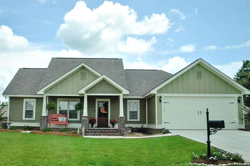 Transitional Craftsman style home with green siding and large front porch with red bench