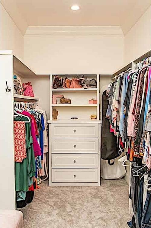 Neatly organized master closet in French style home