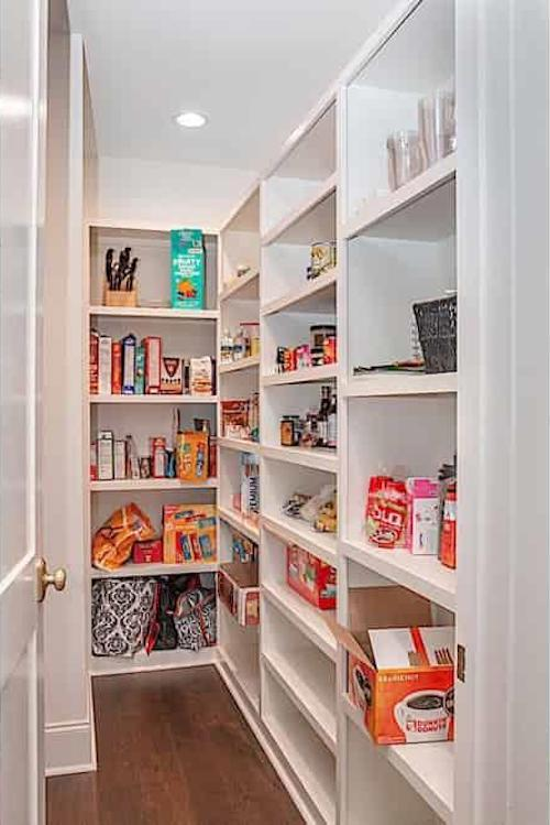 Walk-in kitchen pantry with supplies stocked on shelves