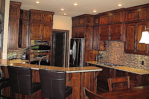 Dark wood kitchen cabinets and lighter-colored granite countertop