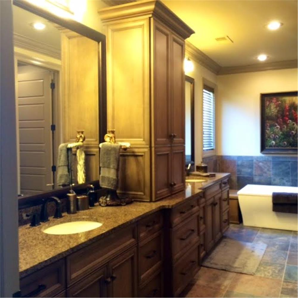 Two bathroom vanity areas separated by a cabinet in House Plan #153-2019