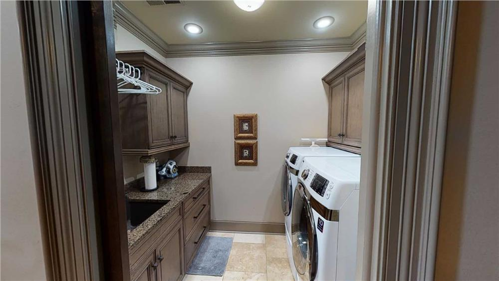 Laundry room with crown molding and baseboard that match in color