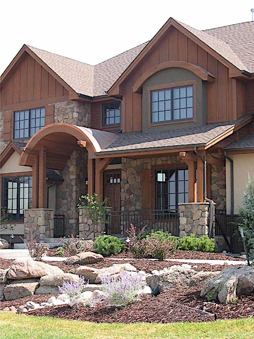 Landscaping in front of a luxurious rustic mountain home