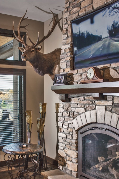 Stone fireplace and elk-head wall decoration in Great Room with rustic vibe