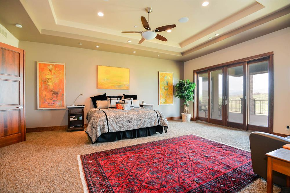 Tray ceiling with ceiling fan and recessed lights in a master bedroom