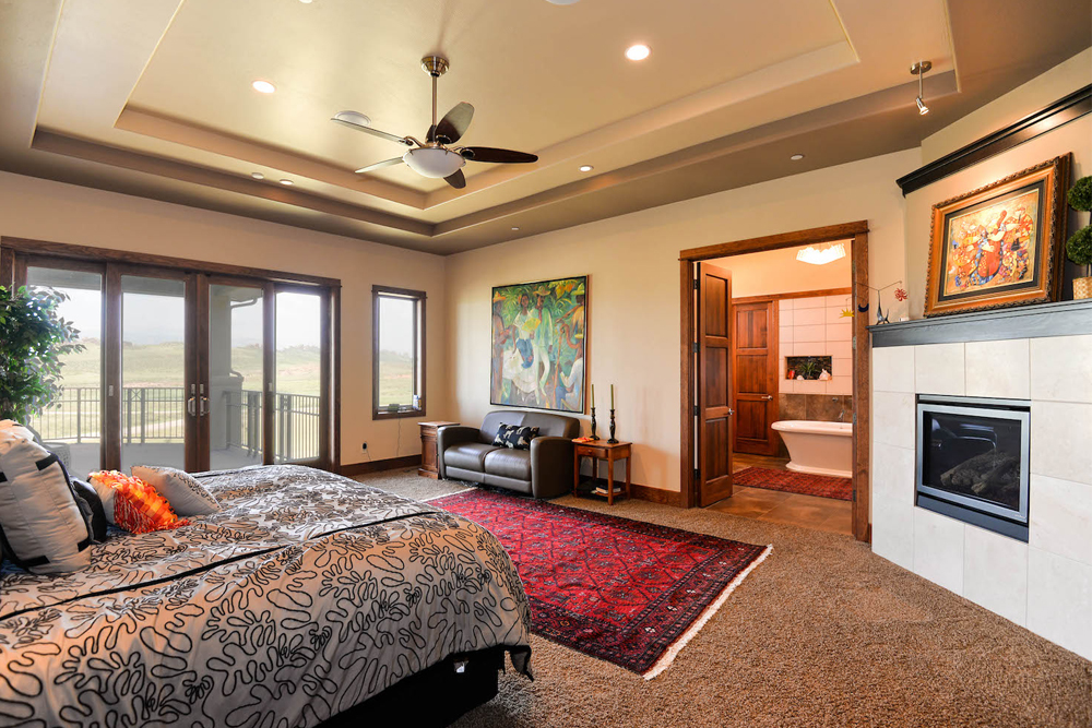 Master bedroom with high ceiling that has a tray design