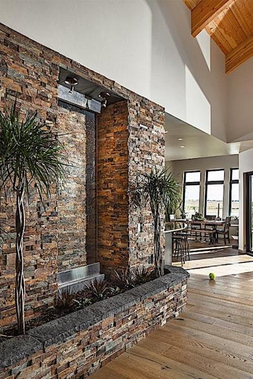 Indoor garden and water feature on stone wall in Contemporary style home
