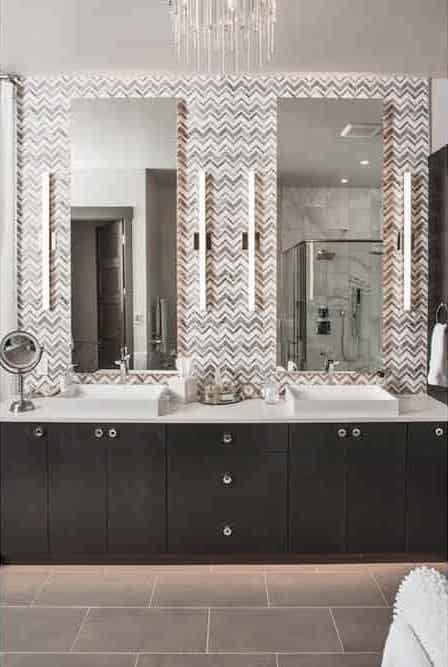 Double vanity bathroom with lighting at the sides of the mirrors
