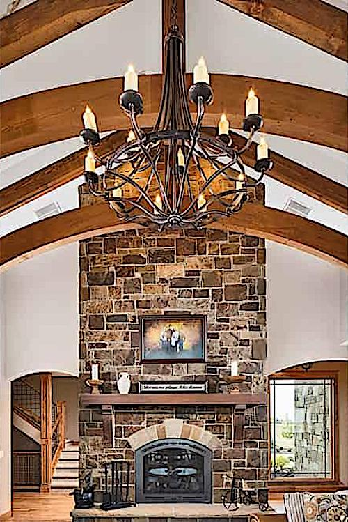 Great room with beautiful stone fireplace and chimney and vaulted timber ceiling