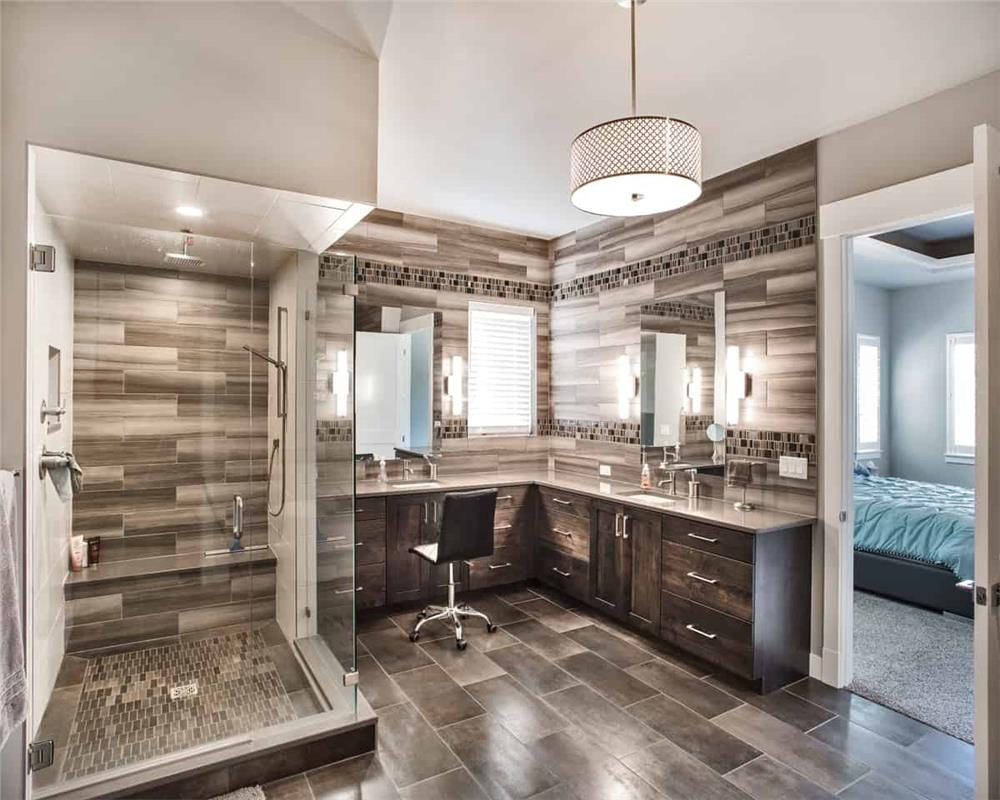 Master bath with glass shower and stone-like tile on the walls and floor