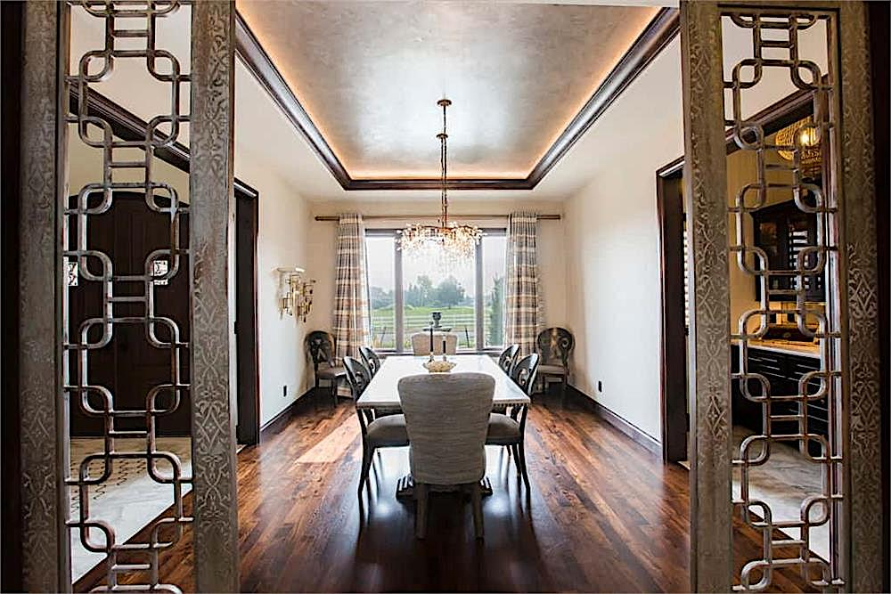 Dining room with tray ceiling outlined by dark brown crown molding
