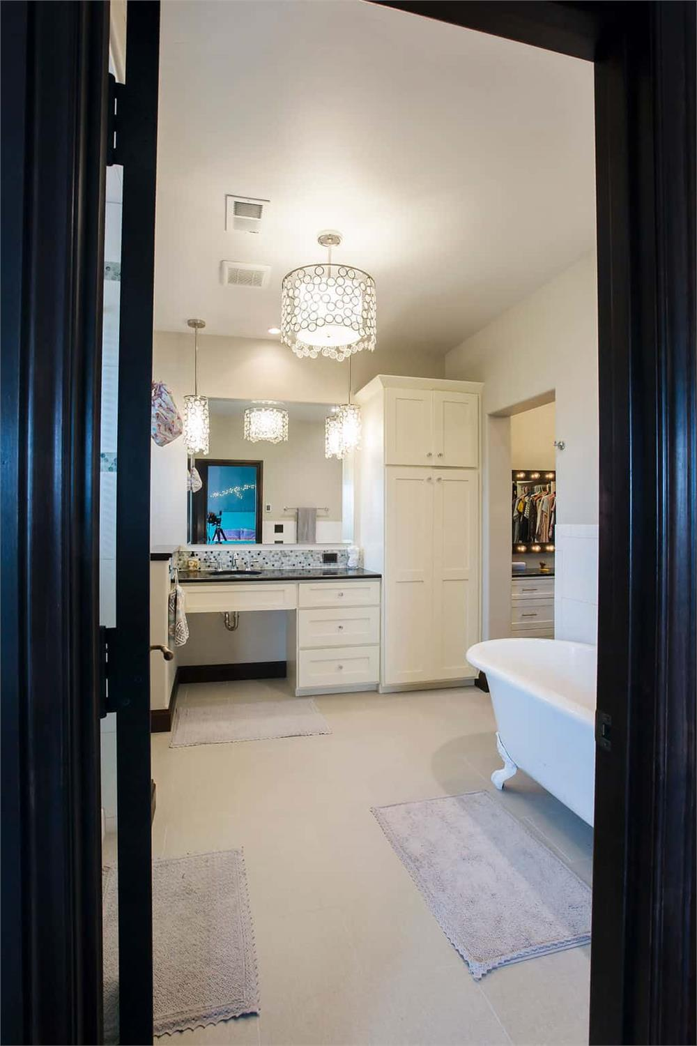 Master bathroom with hanging lights at the mirrors and a large hanging ambient light fixture
