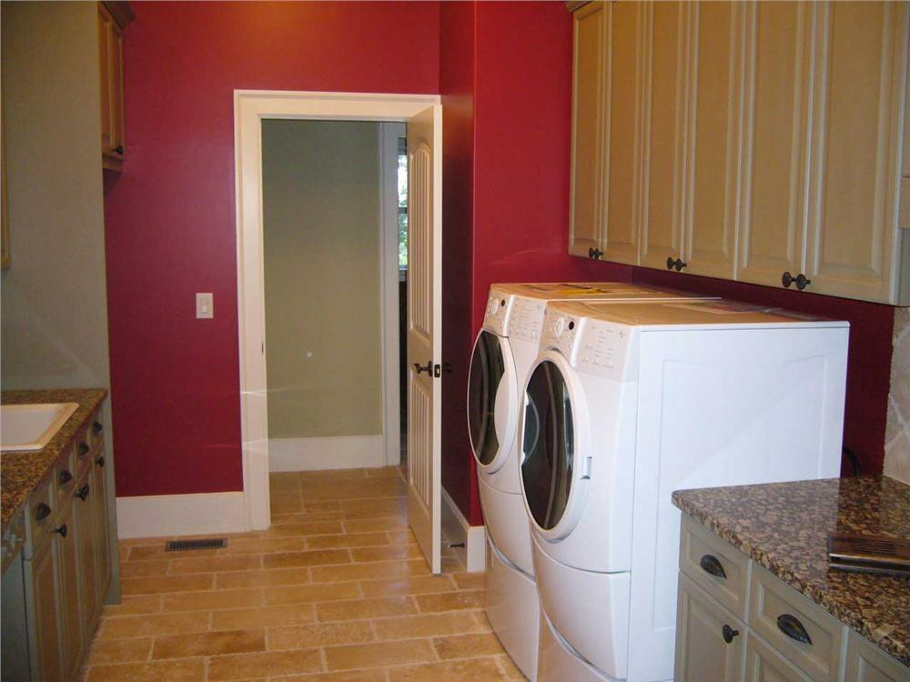 Red laundry room with countertops and cabinets