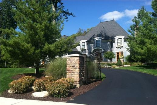 European style home with curved driveway leading past home courtyard entry to 4-car garage area